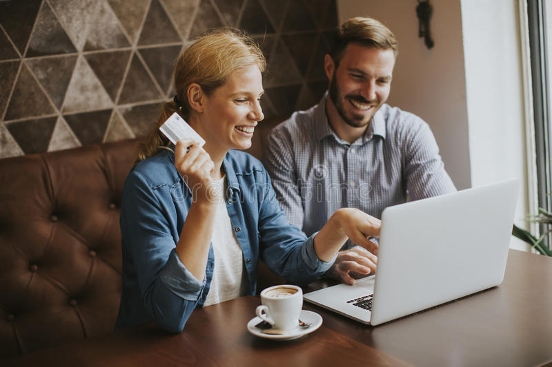 Couple buying online with credit card and laptop in a coffee shop. View at couple buying online with credit card and laptop in a coffee shop royalty free stock photography