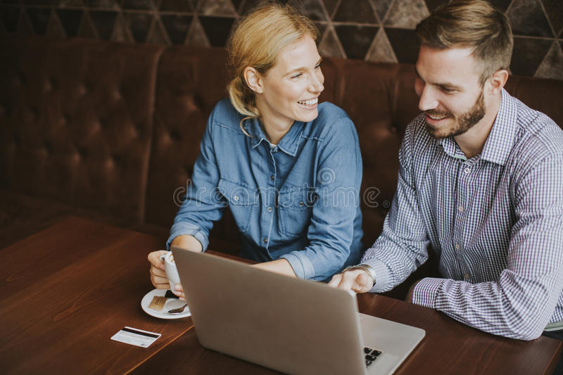 Couple buying online with credit card and laptop in a coffee sho. View at couple buying online with credit card and laptop in a coffee shop stock photos