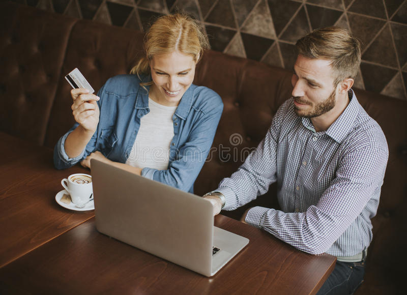 Couple buying online with credit card and laptop in a coffee shop. View at couple buying online with credit card and laptop in a coffee shop royalty free stock photos