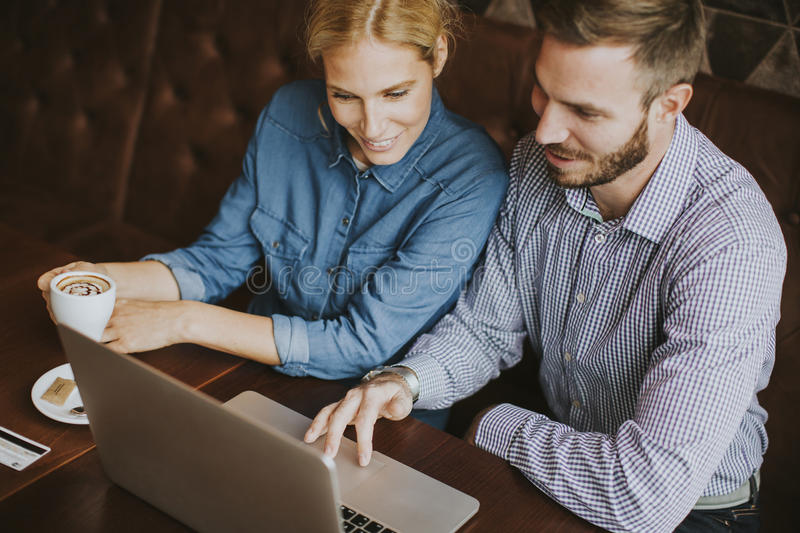 Couple buying online with credit card and laptop in a coffee shop. View at couple buying online with credit card and laptop in a coffee shop royalty free stock photo
