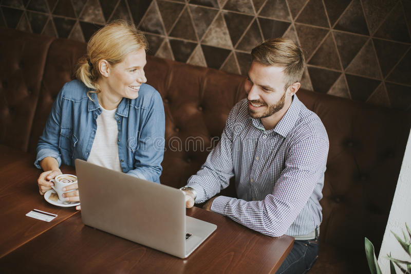 Couple buying online with credit card and laptop in a coffee shop. View at couple buying online with credit card and laptop in a coffee shop stock photography