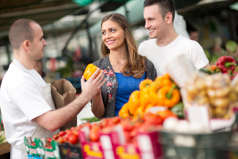 Couple buying from salesman at street market. Couple buying vegetable from salesman at street market royalty free stock image