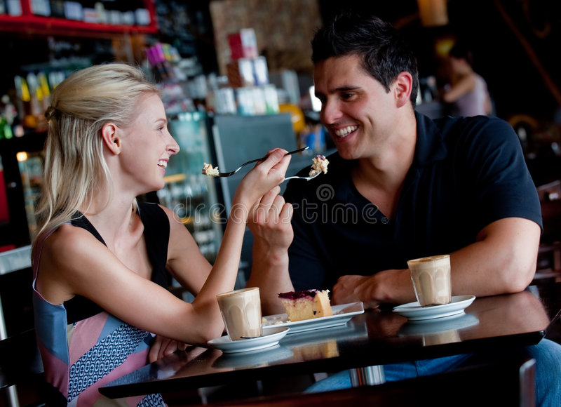 Couple In Cafe. A young attractive couple sitting together in a cafe with coffee ad cake