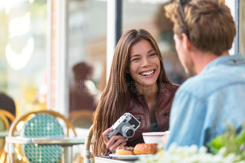 Couple at cafe lifestyle. Young tourists eating breakfast at restaurant table outside sidewalk terrace at parisian bistro in. European city. Asian women royalty free stock photography