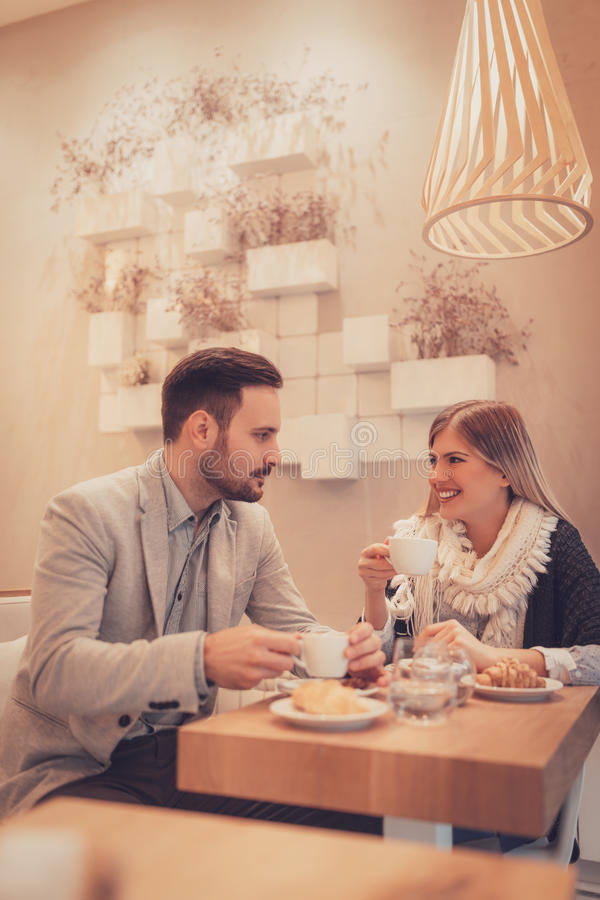 Couple In A Cafe. Young men and young women sitting at cafe and talking with smile. They drinking coffee and having breakfast royalty free stock photography