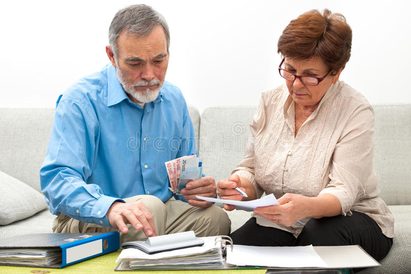 Couple calculating home finances. Senior couple worrying about their money situation stock photography