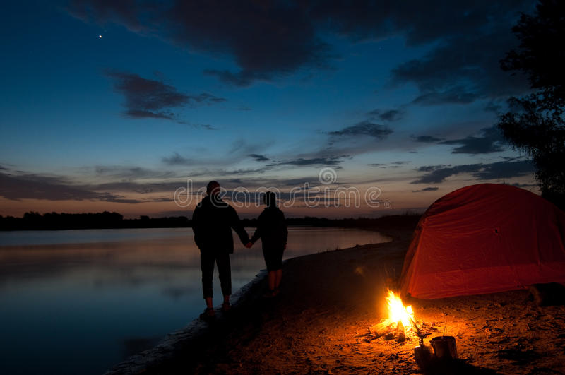 Couple camping near lake. Couple tent camping in the wilderness stock photography