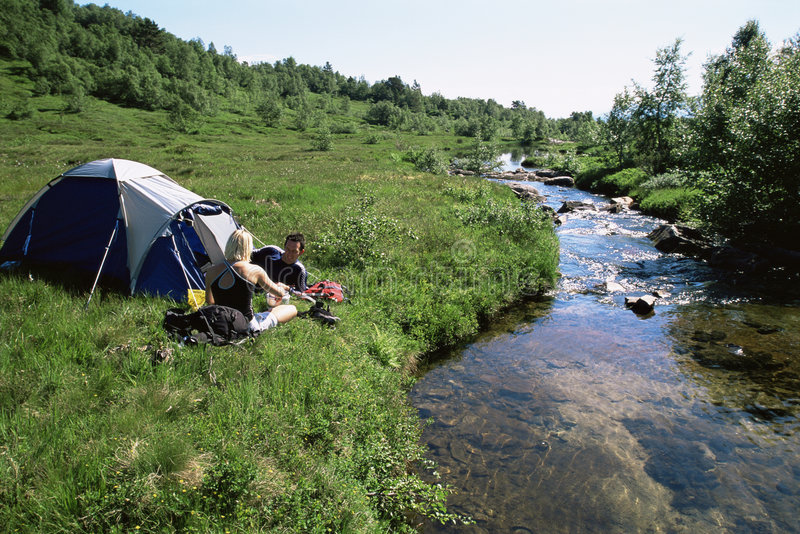 Couple camping next to stream royalty free stock image