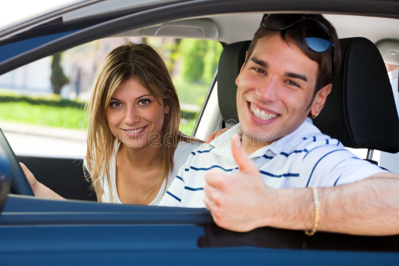 Couple in car. Young couple in car showing thumbs up