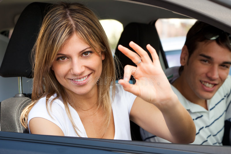 Couple in car. Young couple in car showing okay sign