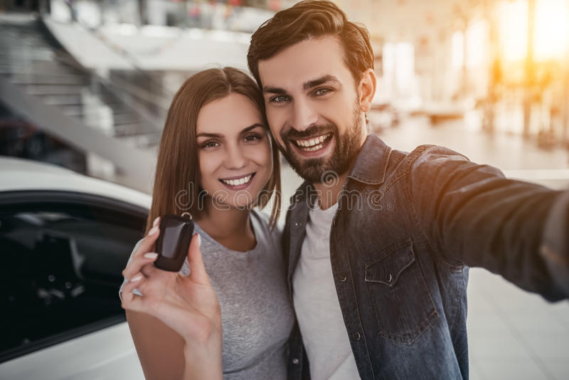 Couple at car dealership. Happy beautiful couple is choosing a new car at dealership. Man is making photo while women is taking keys in hand stock photo