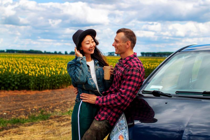 Couple on car road trip travel having coffee break outdoors smiling happy. stock images