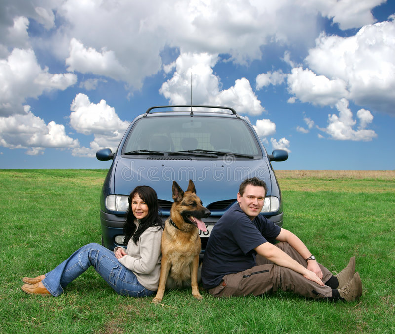 Couple On A Car Trip. Couple and a dog sitting on a grass in front of a car royalty free stock photo