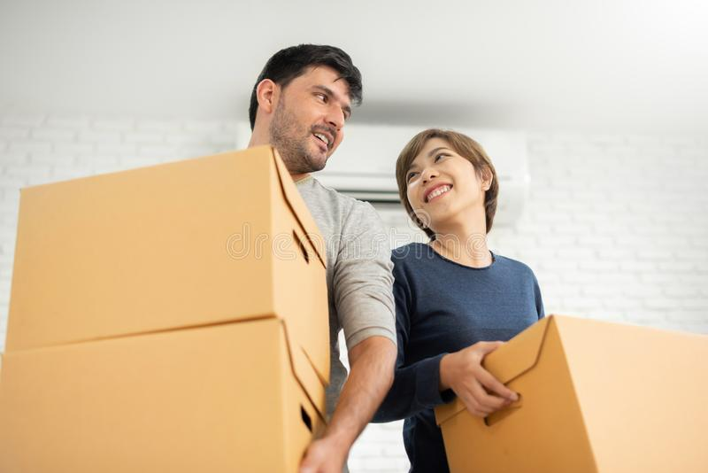 Couple with cardboard boxes at new home. stock images