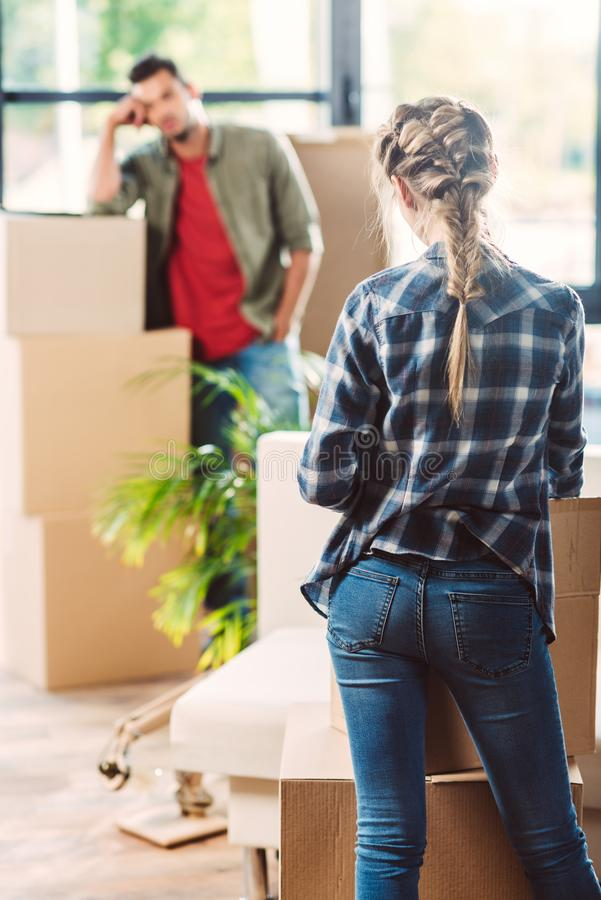 Couple with cardboard boxes in new house stock photography