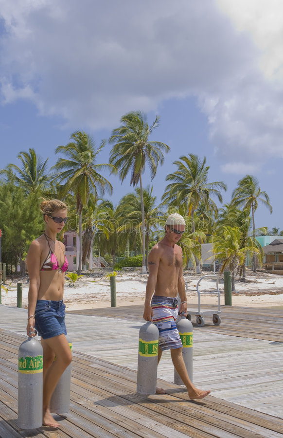 Couple carrying Scuba Tanks in the Caribbean. Handsome Couple carrying Scuba Tanks in the Caribbean royalty free stock photography