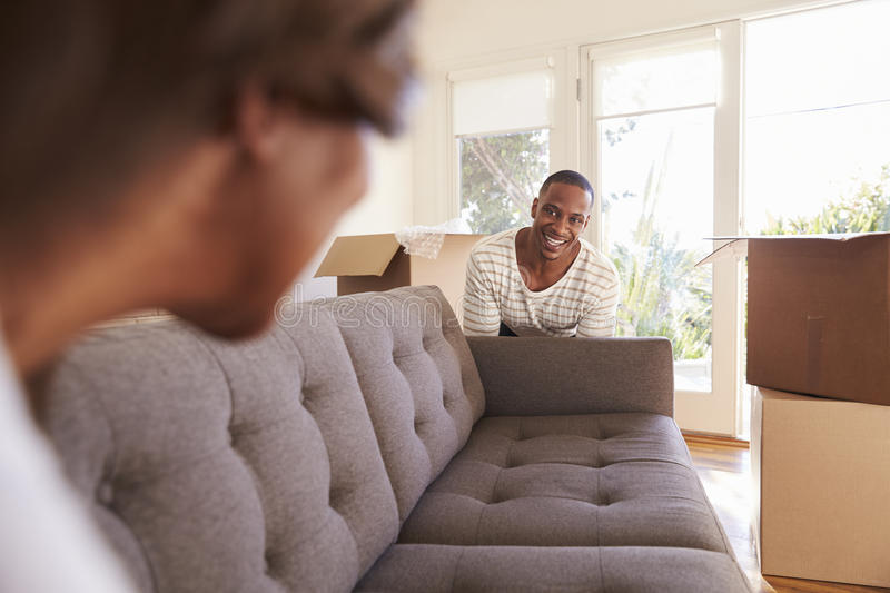 Couple Carrying Sofa Into New Home On Moving Day stock image