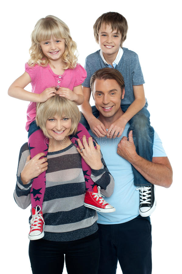 Couple carrying their children on shoulders stock image