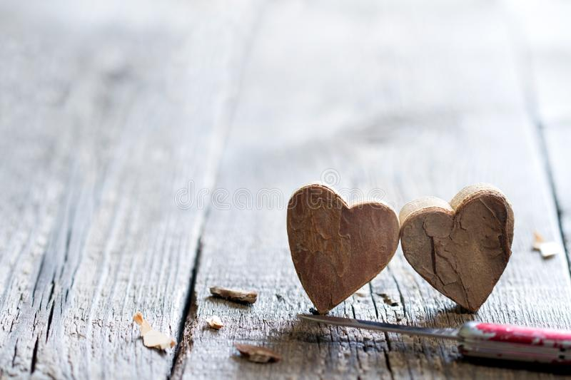 Couple carved wooden hearts and knife abstract love valentines background with free space. Closeup stock photos