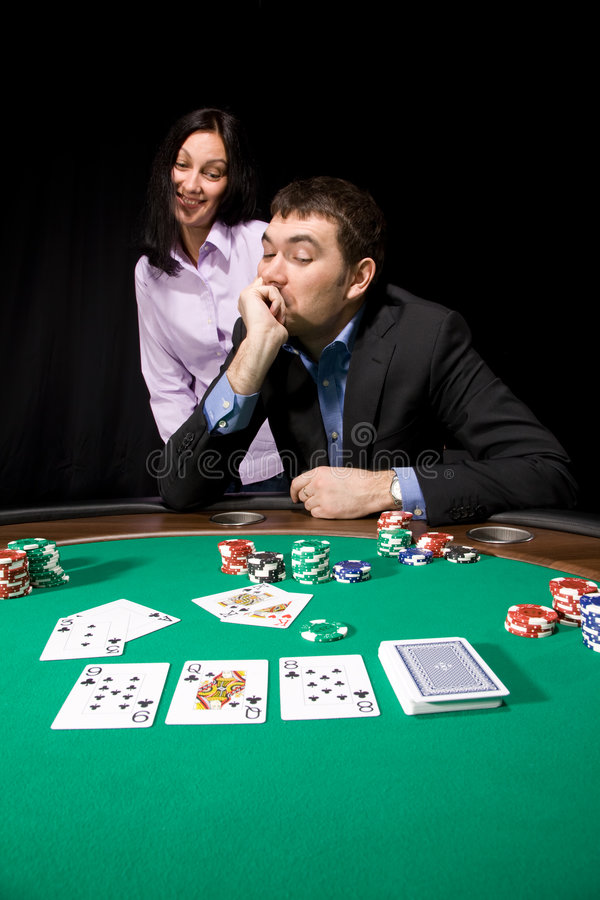 Couple in the casino. Playing poker on green felt stock image