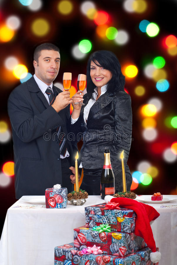 Couple celebrate Christmas night. Elegant couple holding glasses with champagne and celebrate Christmas night together with lights around them