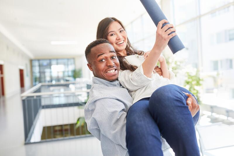 Couple celebrate university completion. Happy interracial couple celebrate university diploma completion stock photos