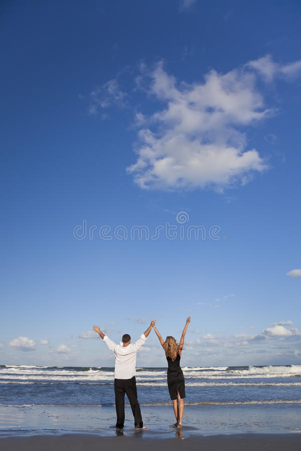 Couple Celebrating Arms Raised On A Beach stock image