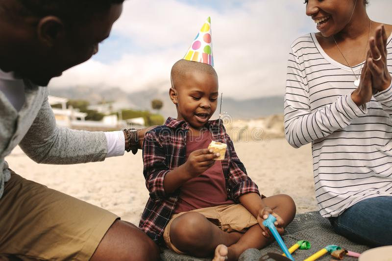 Couple celebrating birthday of their son at the beach royalty free stock photography