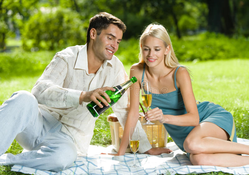 Couple celebrating with champagne at picnic. Young couple celebrating with champagne at picnic royalty free stock image