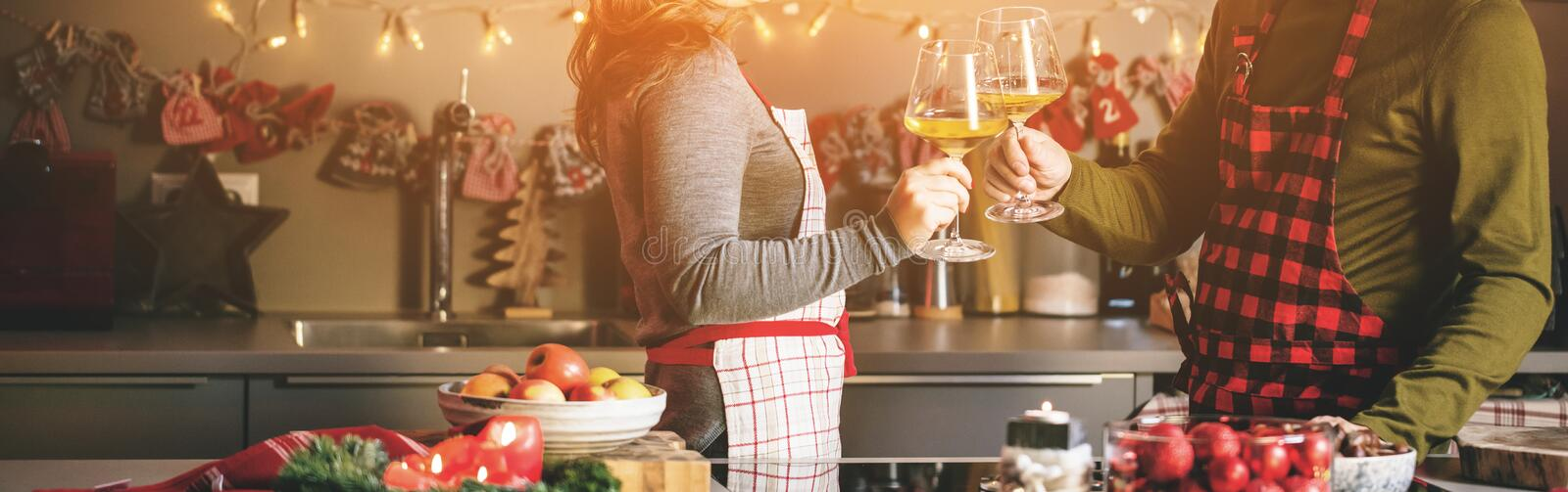 Couple celebrating Christmas in the kitchen and drink wine stock images