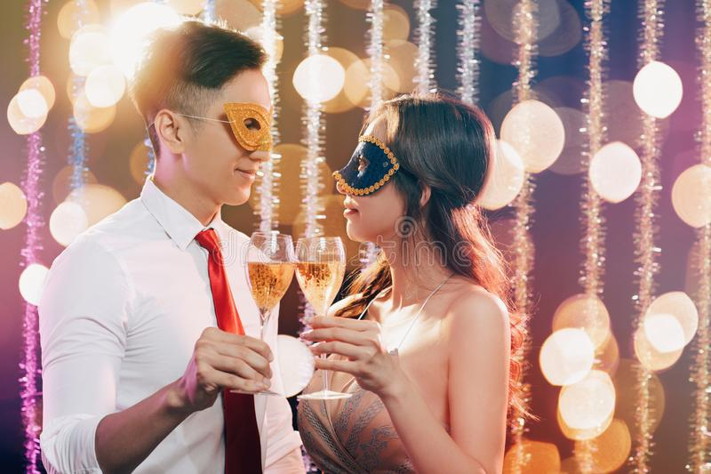 Couple celebrating New Year and drinking champagne on masquerade party royalty free stock image
