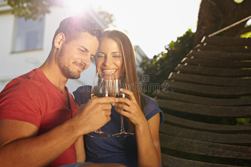 Couple celebrating with wine in backyard. Outdoor shot of young caucasian couple in backyard toasting wine smiling. Romantic couple relaxing on hammock stock photography