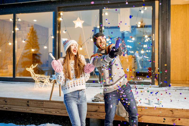 Couple celebrating winter holidays in front of the house outdoors royalty free stock images