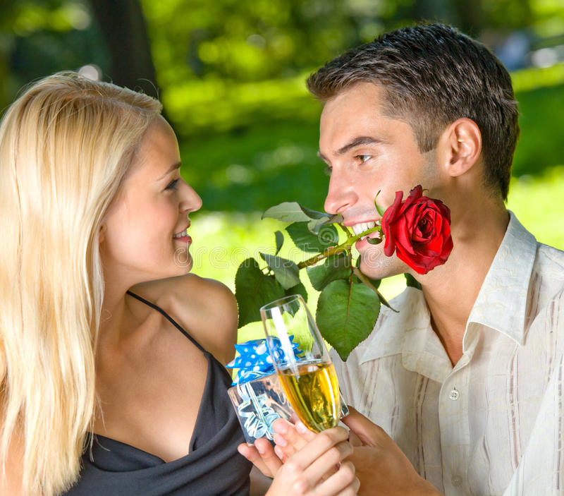 Couple with champagne. Couple with gift and rosa, outdoors royalty free stock photography