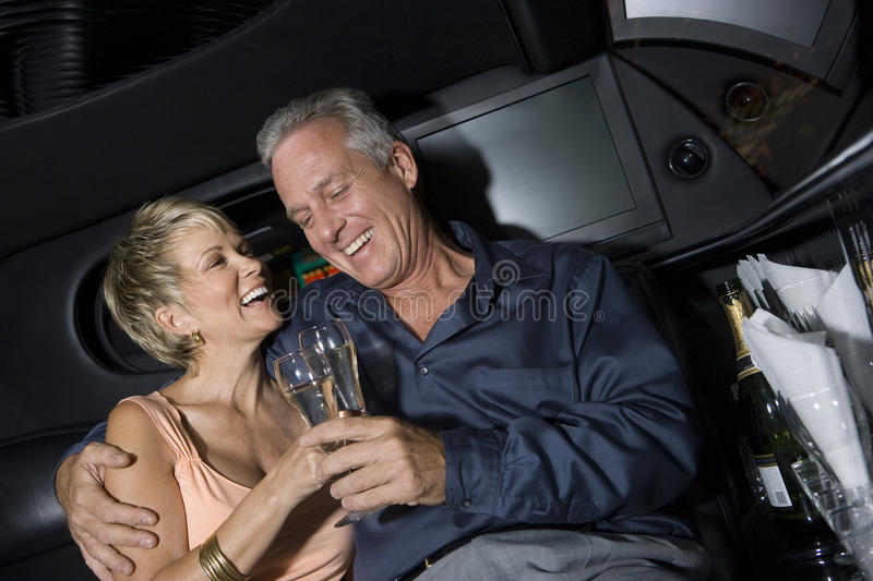 Couple With Champagne Sitting In Limousine