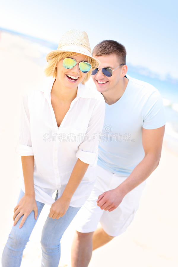 Couple chasing at the beach stock image