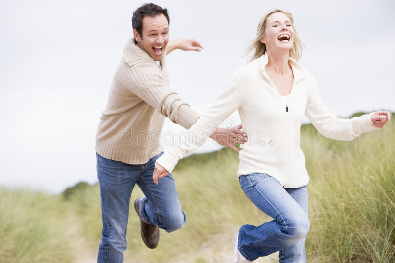 Couple chasing one another through dunes stock photography
