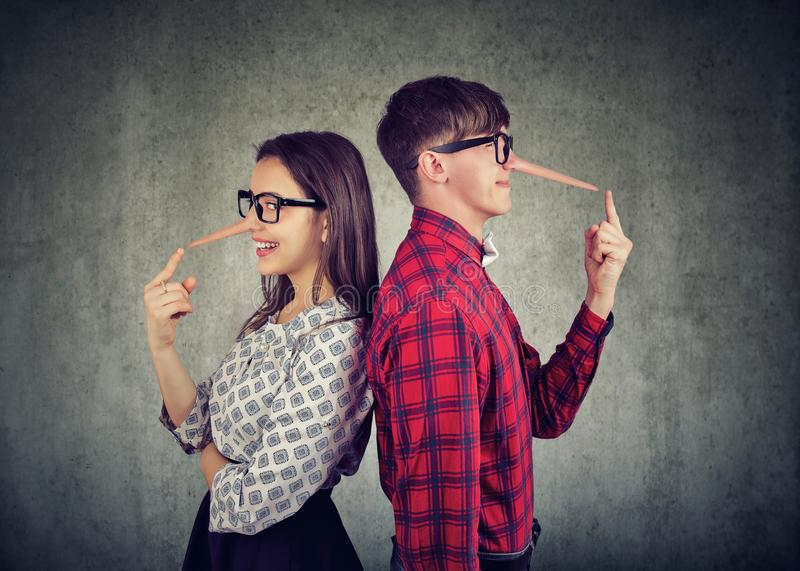 Couple of cheaters, satnding back to back two liars stock photos