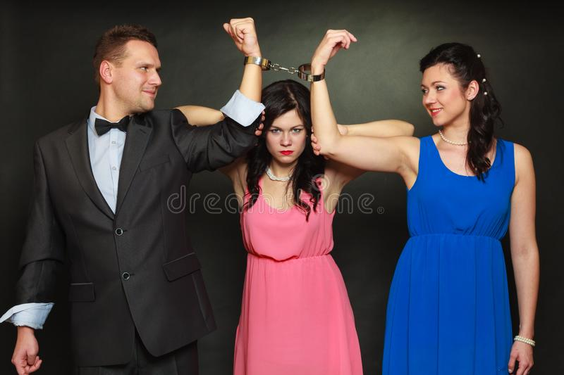 Wife and husband in handcuffs woman standing behind royalty free stock photography