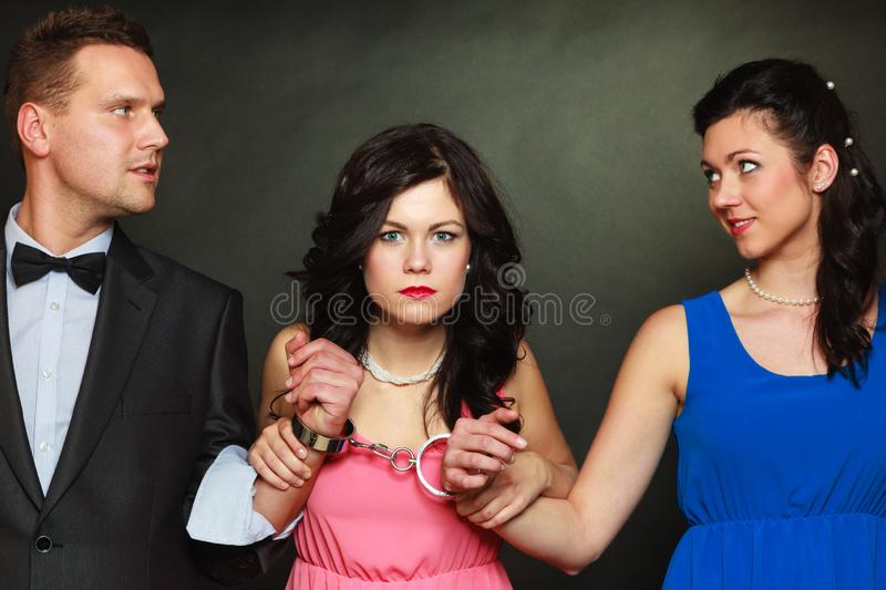 Wife and husband in handcuffs woman standing behind stock photos