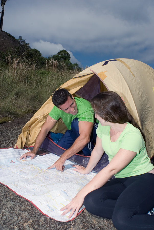 Couple Checking a Map. Young couple checking their route on a map in front of their tent with ominous gray clouds gathering overhead royalty free stock photos