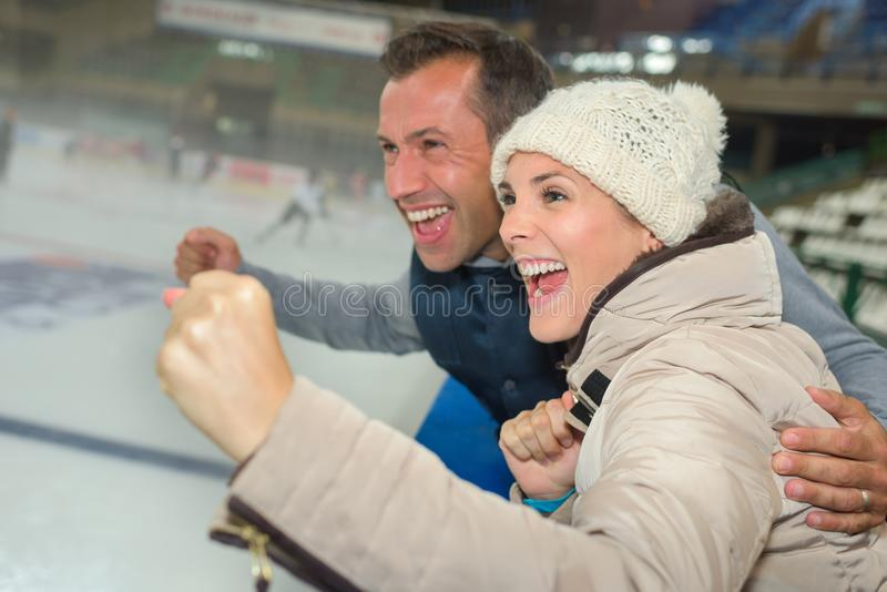 Couple cheering on their ice hockey team. Spectator stock images