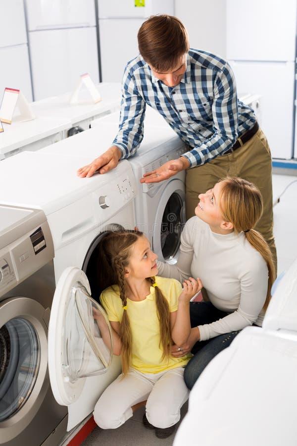 Couple with child buying washing machine royalty free stock photos