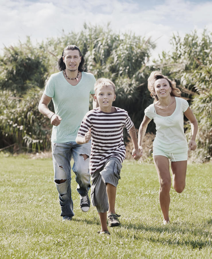 Couple with child playing running in summer royalty free stock photo