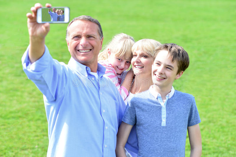 Couple and children taking family picture royalty free stock images