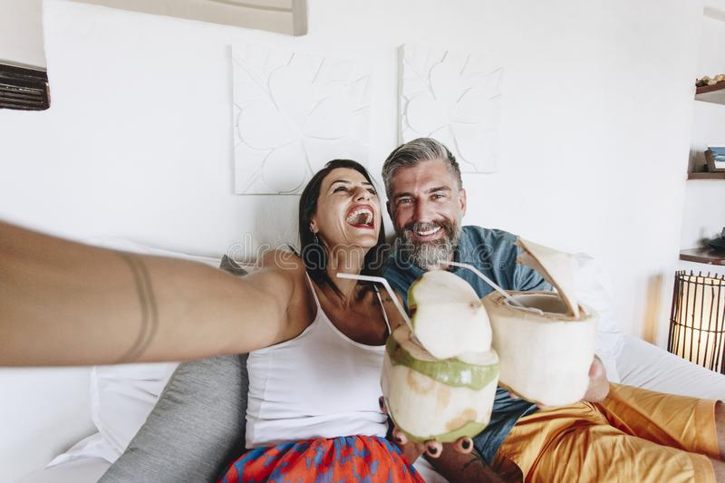 Couple chill on bed drinking coconut juice stock photos