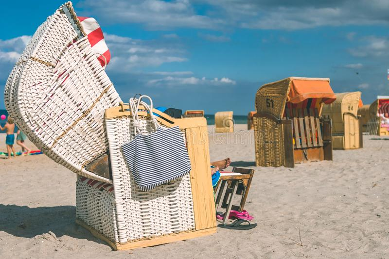 Couple chill relax in striped roofed chairs on sandy beach in Travemunde., Lubeck, Germany.  royalty free stock images