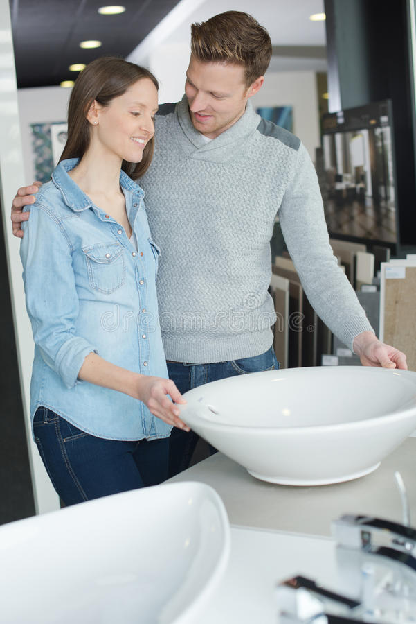 Couple chooses bathroom furniture in home improvement store royalty free stock photography