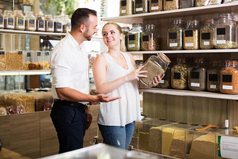 Couple chooses dried herbs. Cheerful couple having jar with dried herbs in hands in shop with ecological goods royalty free stock photos
