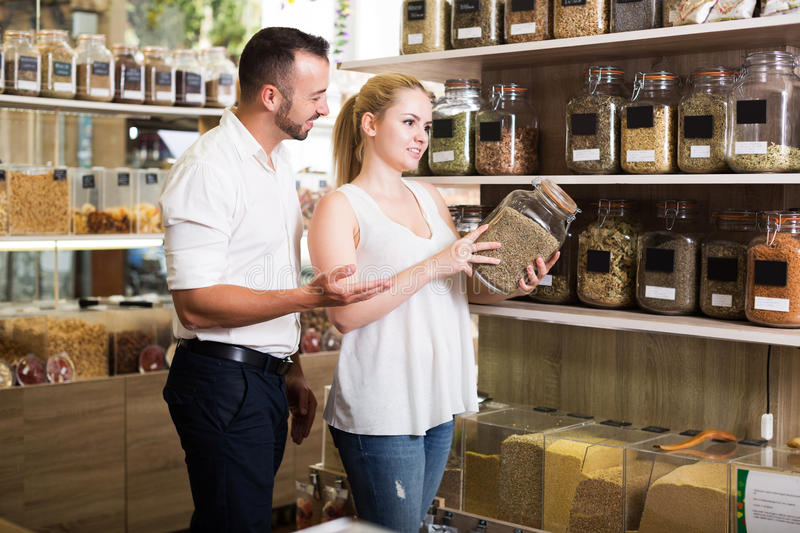 Couple chooses dried herbs. Happy young couple having jar with dried herbs in hands in shop with ecological goods stock image